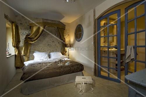 schlafzimmer mit doppelbett betthimmel aus goldfarbenen vorh ngen ge ffneter glast r zum bad. Black Bedroom Furniture Sets. Home Design Ideas