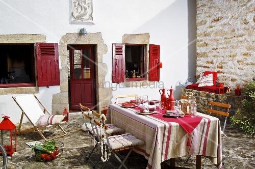 gedeckter tisch auf terrasse vor haus mit roter t r roten fensterl den bild kaufen. Black Bedroom Furniture Sets. Home Design Ideas