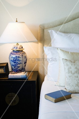lampe mit blau weissem porzellanfuss auf beistelltisch neben bett bild kaufen living4media. Black Bedroom Furniture Sets. Home Design Ideas