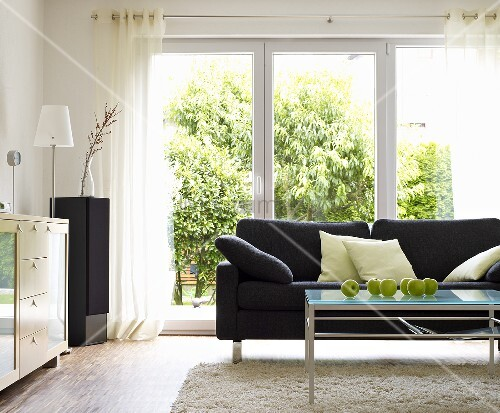 Wohnzimmer mit grauem Sofa & Couchtisch aus Glas vor