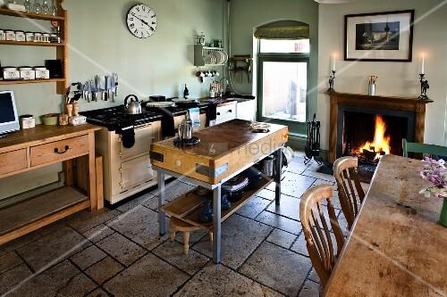 l ndliche k che mit steinboden hackstock esstisch und kaminfeuer bild kaufen living4media. Black Bedroom Furniture Sets. Home Design Ideas