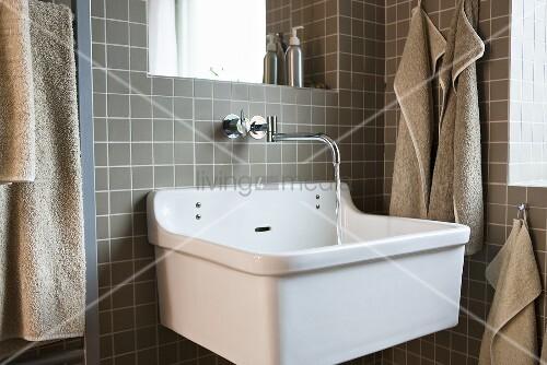 badezimmerecke ausgussbecken mit wandarmatur vor grauen fliesen und geh ngten handt chern. Black Bedroom Furniture Sets. Home Design Ideas