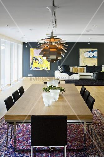 esstisch mit holzplatte und designerlampe im offenen wohn. Black Bedroom Furniture Sets. Home Design Ideas