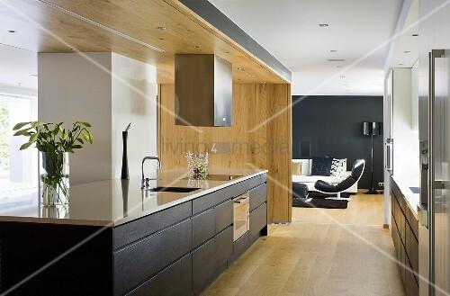 offene k che k chenblock mit gl nzender arbeitsplatte und schwarzen schubl den vor raumteiler. Black Bedroom Furniture Sets. Home Design Ideas