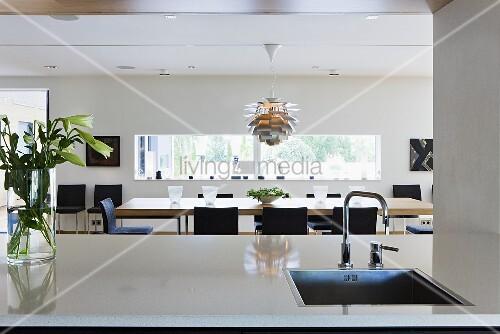 offene k che sp le im k chenblock und blick auf den esstisch mit designerlampe bild kaufen. Black Bedroom Furniture Sets. Home Design Ideas