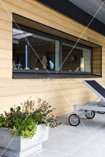 fensterband in holzfassade und pflanzenk bel auf der. Black Bedroom Furniture Sets. Home Design Ideas