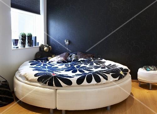 schlafraumecke rundes bett mit blumenmuster auf bettw sche vor schwarzer wand bild kaufen. Black Bedroom Furniture Sets. Home Design Ideas