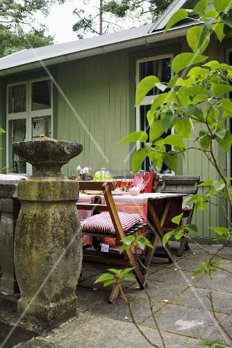gedeckter tisch auf steinterrasse vor gr nem holzhaus bild kaufen living4media. Black Bedroom Furniture Sets. Home Design Ideas