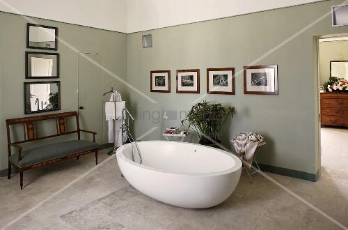 freistehende badewanne vor grauen w nden auf steinboden und antike sitzbank bild kaufen. Black Bedroom Furniture Sets. Home Design Ideas