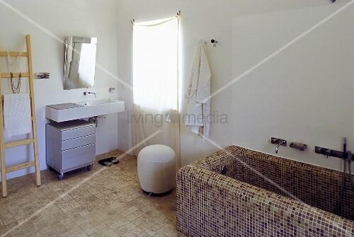 l ndliches bad badewanne mit braunen mosaikfliesen und waschtisch mit spiegel am fenster. Black Bedroom Furniture Sets. Home Design Ideas