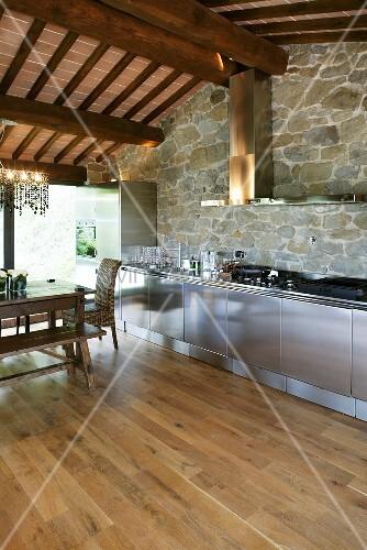edelstahlküche vor natursteinwand und holzbalkendecke im,