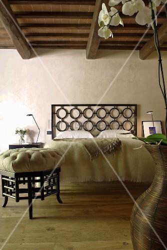 renoviertes landhaus mit rustikaler holzbalkendecke hocker im asienstil und bett mit kopfteil. Black Bedroom Furniture Sets. Home Design Ideas