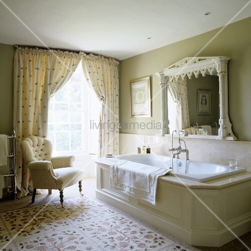A Spacious Traditional English Country House Style Bathroom With Floor To Ceiling Windows And A Comfortable Armchair