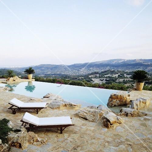 liegest hle auf natursteinboden vor pool mit ausblick auf die spanische landschaft bild kaufen. Black Bedroom Furniture Sets. Home Design Ideas