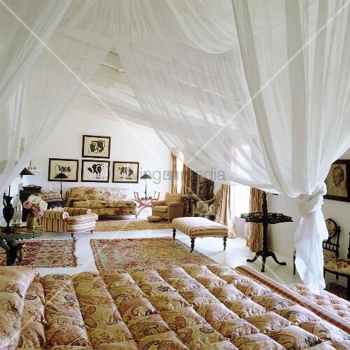 weisser stoffhimmel ber bett und elegante sitzm bel mit teppichen im offenen schlafraum bild. Black Bedroom Furniture Sets. Home Design Ideas