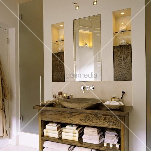 holzwaschtisch mit rustikaler holzschale und spiegel neben beleuchtetem einbauregal bild. Black Bedroom Furniture Sets. Home Design Ideas