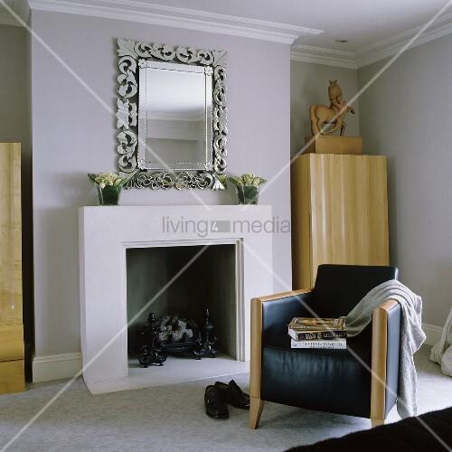 schwarzer ledersessel vor dem kamin mit spiegel im silberrahmen bild kaufen living4media. Black Bedroom Furniture Sets. Home Design Ideas