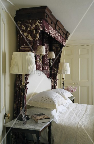 Table and wall lamps next to and above a double bed with patterned canopy and white bed linen ...