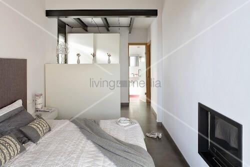 schlafraum mit eingebautem fernseher und halbhohem raumteiler mit blick in badraum bild kaufen. Black Bedroom Furniture Sets. Home Design Ideas