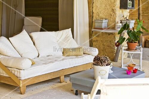 sofa mit einfachem holzgestell und gro en weissen kissen auf der terrasse eines rustikalen. Black Bedroom Furniture Sets. Home Design Ideas