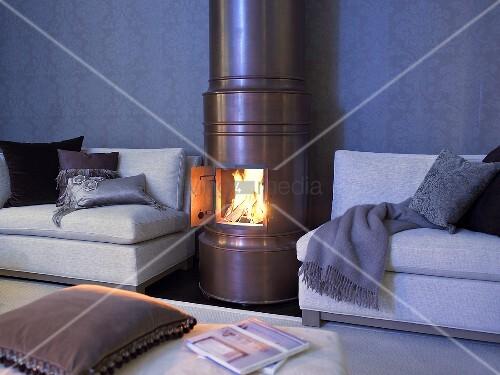 kupferfarbener kaminofen mit offener t r und blick auf feuer neben sofa mit kissen und decke. Black Bedroom Furniture Sets. Home Design Ideas