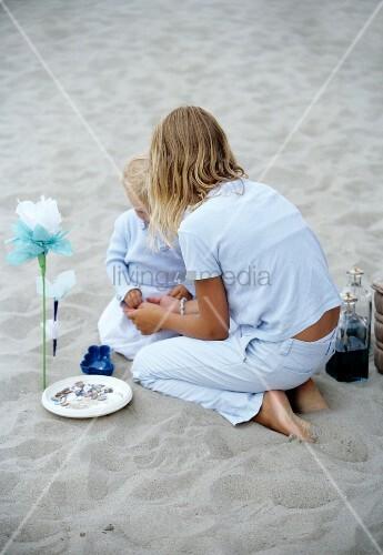 m dchen spielt mit kleinem kind im sand bild kaufen living4media. Black Bedroom Furniture Sets. Home Design Ideas