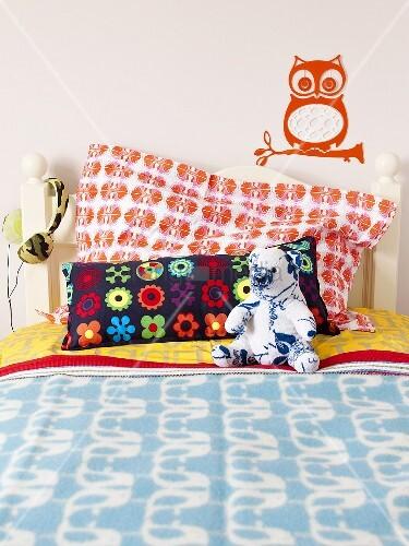 kinderbett mit bunten kissen kuscheltier und kopfh rer. Black Bedroom Furniture Sets. Home Design Ideas