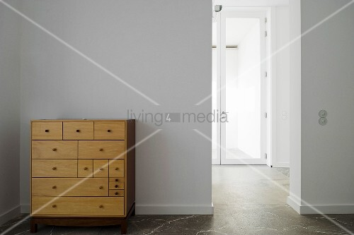 schlichte holzkommode vor weisser wand und offener durchgang mit blick auf glast r bild kaufen. Black Bedroom Furniture Sets. Home Design Ideas