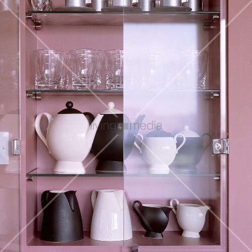 schwarzweisse kannen und gl ser im rosalackierten schrank mit offener glast r bild kaufen. Black Bedroom Furniture Sets. Home Design Ideas
