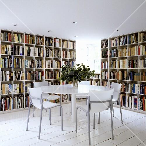 runder tisch vor wandhohen b cherregalen auf weissen. Black Bedroom Furniture Sets. Home Design Ideas