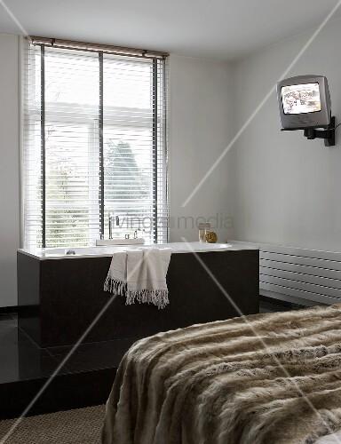 felldecke auf bett und freistehende graue badewanne vor. Black Bedroom Furniture Sets. Home Design Ideas