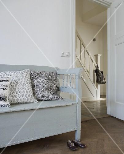 graue sitzbank mit kissen und blick durch offene t r in flur eines landhauses bild kaufen. Black Bedroom Furniture Sets. Home Design Ideas