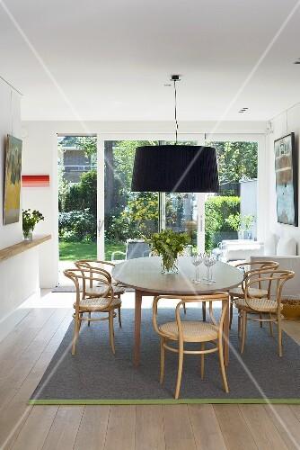 geschwungene rattanst hle um esstisch und h ngelampe mit schwarzem schirm vor terrassenfenster. Black Bedroom Furniture Sets. Home Design Ideas