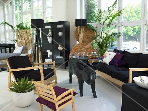 st hle und sofa mit hellem holzrahmen um tisch mit tierfigur vor fensterfront bild kaufen. Black Bedroom Furniture Sets. Home Design Ideas