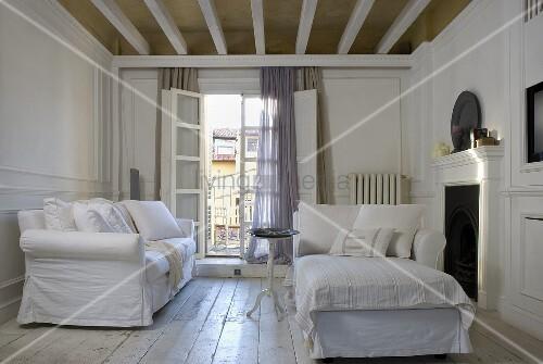 weisse sofagarnitur mit hussen vor offener balkont r und rustikaler dielenboden bild kaufen. Black Bedroom Furniture Sets. Home Design Ideas