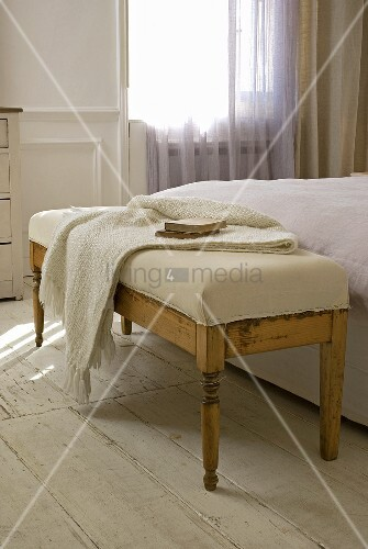 antike bettbank mit hellem polster und strickplaid auf weiss lackiertem dielenboden bild. Black Bedroom Furniture Sets. Home Design Ideas