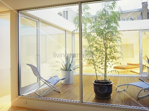 View Through Window To Patio With Wooden Decking And