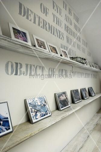 weisse ablage mit photosammlung vor beschrifteter wand bild kaufen living4media. Black Bedroom Furniture Sets. Home Design Ideas