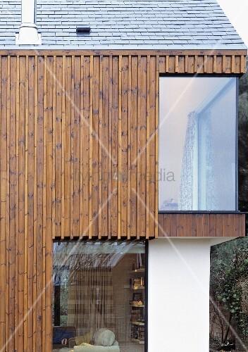 vertikale holzverkleidung am neubauhaus mit raumhohem fenster bild kaufen living4media. Black Bedroom Furniture Sets. Home Design Ideas