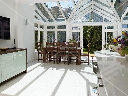 offene k che mit essbereich im wintergarten eines neubauhauses bild kaufen living4media. Black Bedroom Furniture Sets. Home Design Ideas