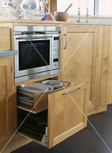 offene schublade mit heller holzfront und geschirr unter backofen bild kaufen living4media. Black Bedroom Furniture Sets. Home Design Ideas