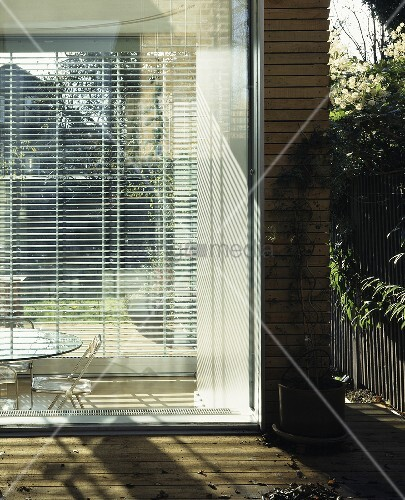 A corner of a house with blinds at the floor to ceiling for Best blinds for floor to ceiling windows