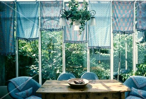 alter holztisch und blaue korbst hle unter schnapprollos in provenzalischen mustern in. Black Bedroom Furniture Sets. Home Design Ideas