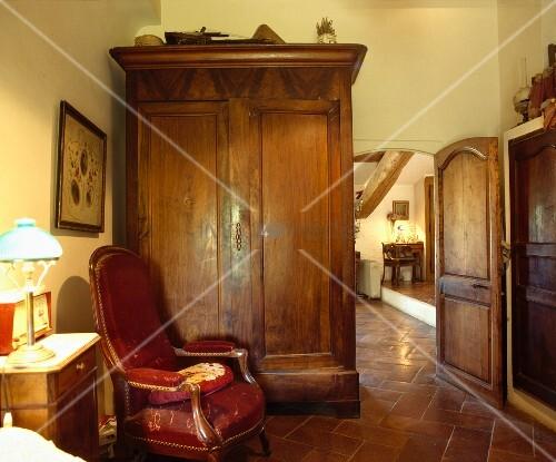 grosser antiker schrank und roter polstersessel in altem. Black Bedroom Furniture Sets. Home Design Ideas