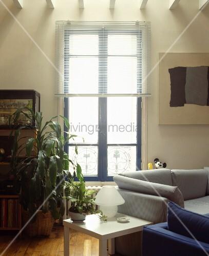 Graues Und Blaues Sofa Korrespondiert Mit Abstrakter Malerei Und Jalousie Vor Blauem