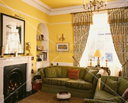 gemusterte vorh nge und gr ne polstersofas neben kamin in gelbem traditionellem wohnzimmer. Black Bedroom Furniture Sets. Home Design Ideas