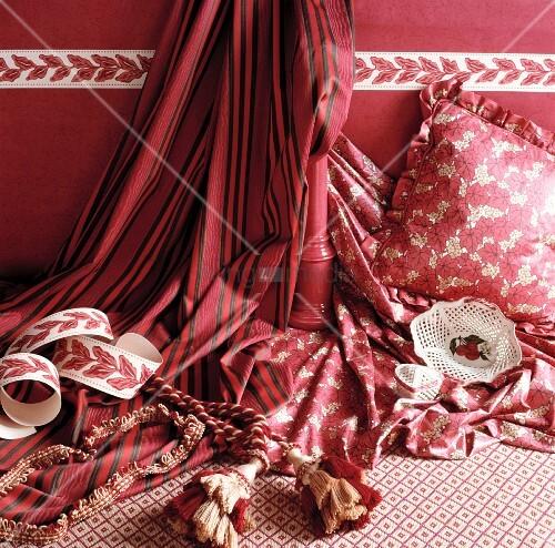 weisse bemalte porzellanschale auf ros gemusterten stoffen und kissen vor wand in dunkelrosa. Black Bedroom Furniture Sets. Home Design Ideas
