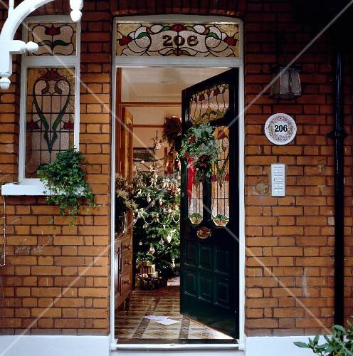 ge ffnete hauseingangst r mit bunten bleiglasfenstern und weihnachtsschmuck in backsteinhaus. Black Bedroom Furniture Sets. Home Design Ideas