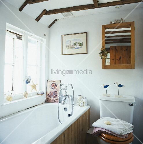 holzrahmenspiegel ber der toilette und eine badewanne mit holzvert felung in einem weissen. Black Bedroom Furniture Sets. Home Design Ideas