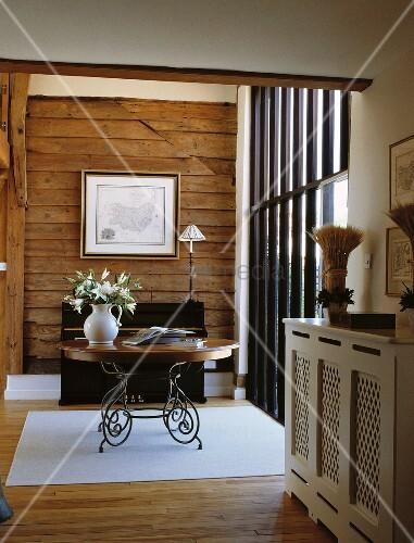 runder holztisch mit geschwungenen metallf ssen vor holzverschalter wand und. Black Bedroom Furniture Sets. Home Design Ideas